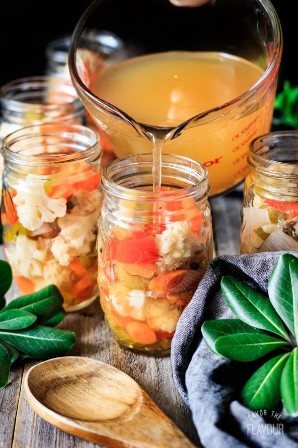 pouring brine into a jar of giardiniera