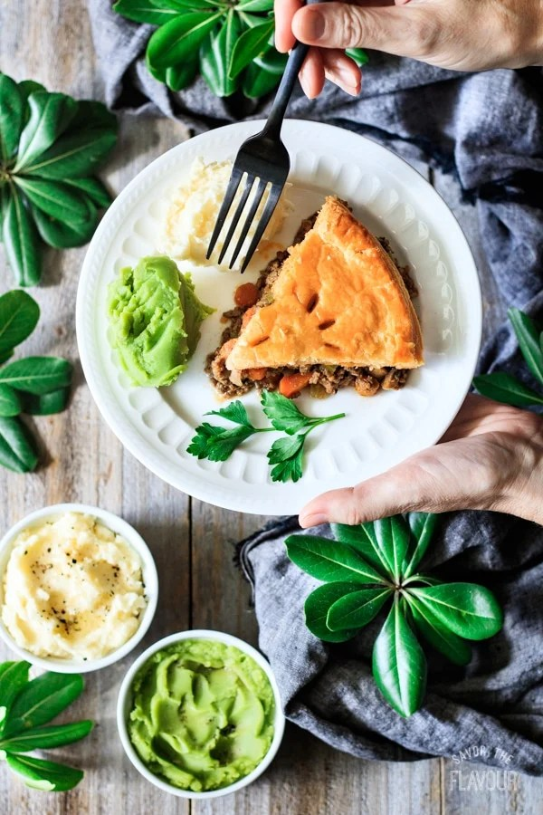 holding a slice of minced beef pie on a plate