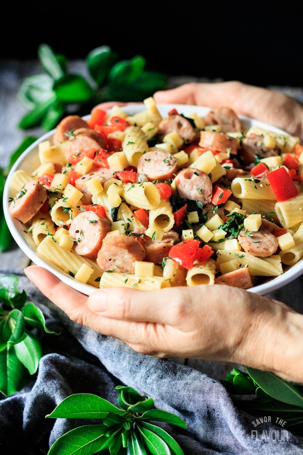 holding a bowl of sausage, pear, and gouda rigatoni