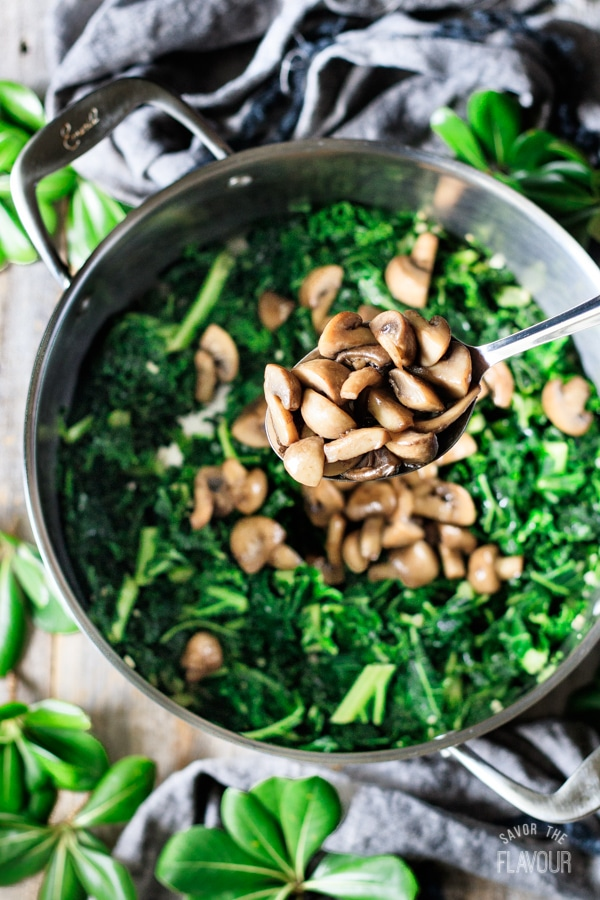 adding mushrooms to sautéed kale