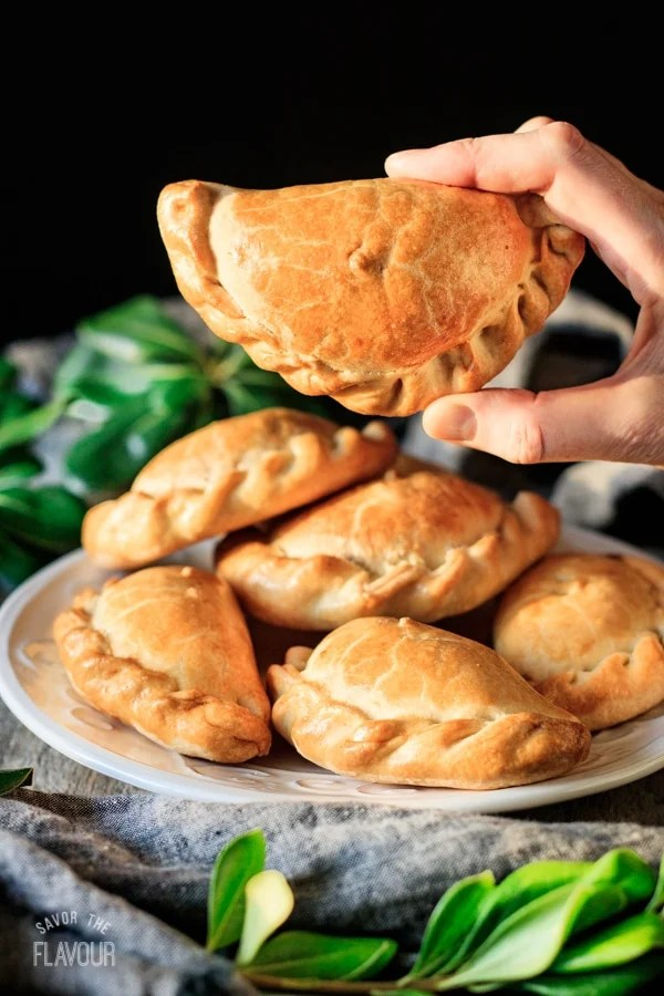holding one of the baked chicken empanadas