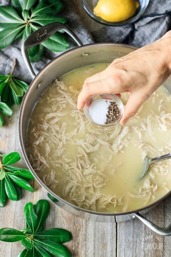 adding salt and pepper to Greek lemon chicken soup