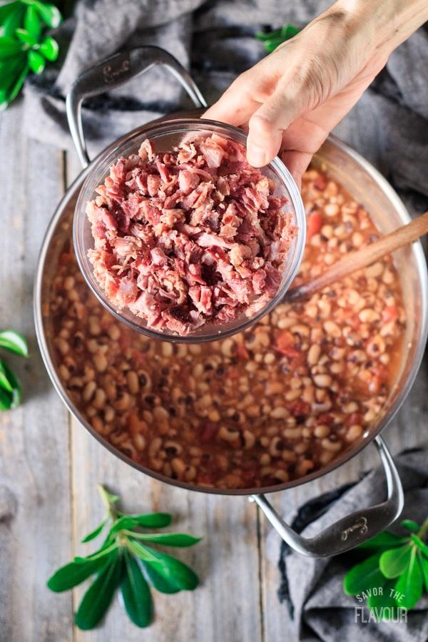 adding the chopped ham to the black eyed peas