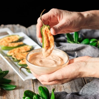 dipping one of the jalapeño poppers into sriracha mayo