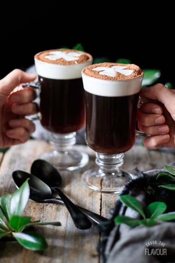 doing a toast with two glasses of non alcoholic Irish coffee