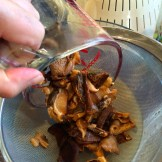 straining the reconstituted dried mushrooms - photo - Karen Anderson