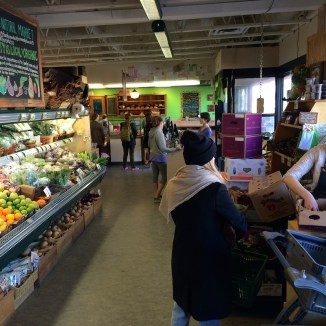 Checking out and chatting is a theme when you know your grocer - photo - Karen Anderson