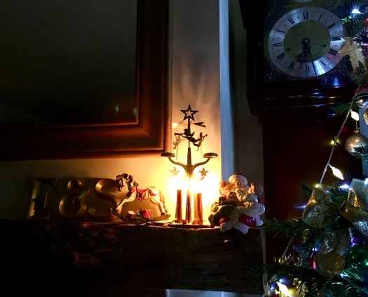 Angel chimes, with lit advent candles on the mantelpiece by the Christmas tree.