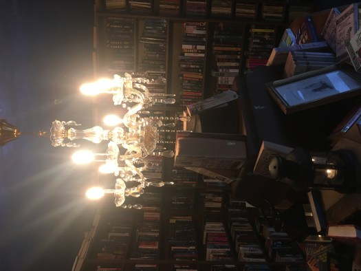 This image is of the Crime Fiction Room. A chandelier grandly illuminating the central criminal display