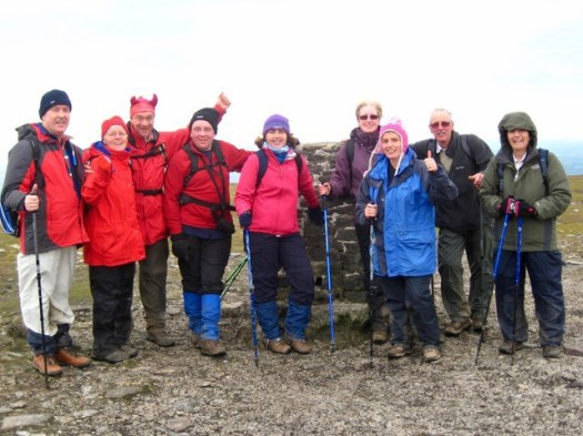 Kathy is at the summit of a monumental walk with a group of fellow walkers