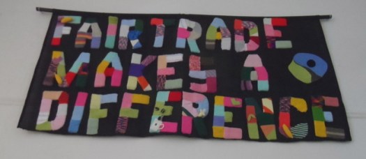 A colourful, appliqued banner declaring 'Fair Trade Makes a Difference'