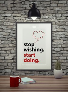 Inspirational quote on picture frame over a dirty brick wall. STOP WISHING. START DOING.