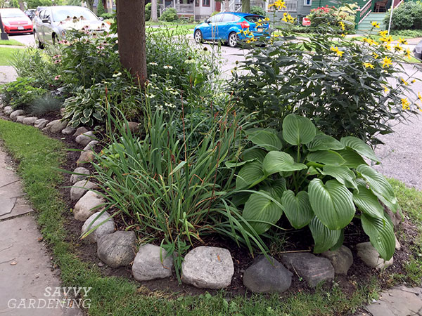 Rocks define a garden space atop a boulevard or hell strip. Though in this case the grass might be hard to cut around the edges!