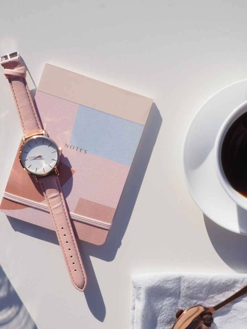 round gold colored analog watch with pink leather strap on pink notebook