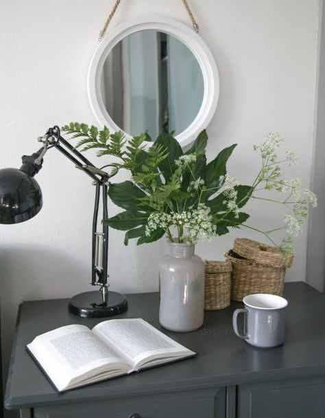 silver and black desk lamp beside brown wooden mug