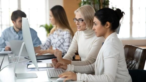 2 women in front of computer