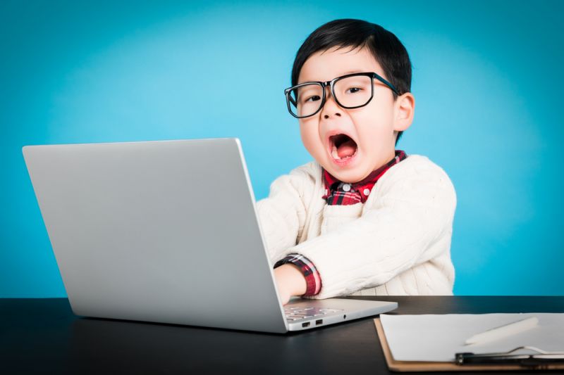 Young child in front of laptop looking surprised