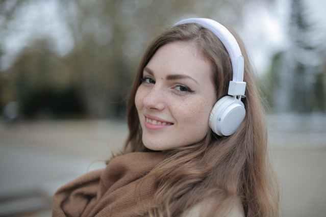 joyful millennial woman in headphones listening to music in park
