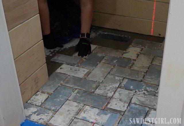 Herringbone brick tile floor next to hardwood floor