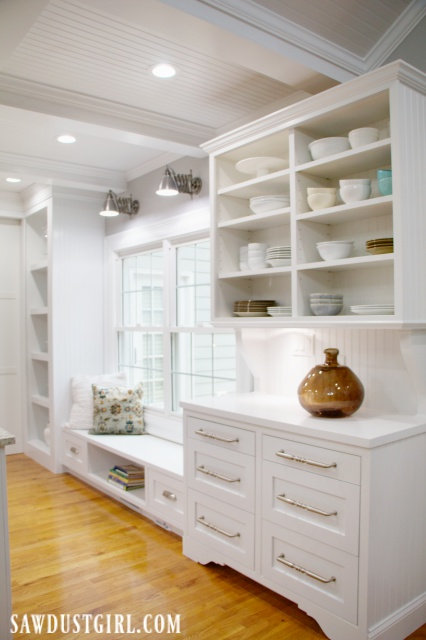 White cabinets in kitchen with window seat and China hutch