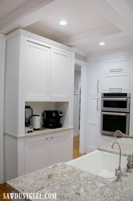 White cabinet, coffee station hutch, built-in double ovens, farmhouse kitchen sink