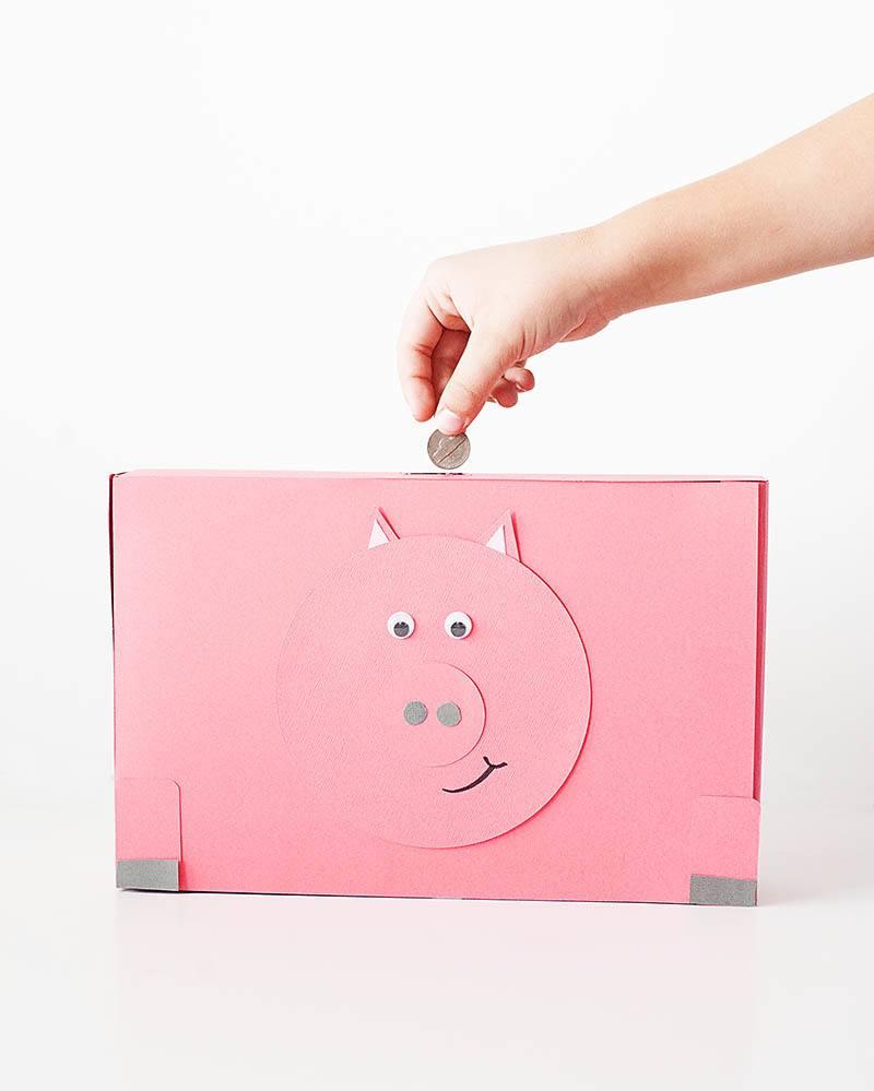 Example of saving money using a cardboard piggy bank.