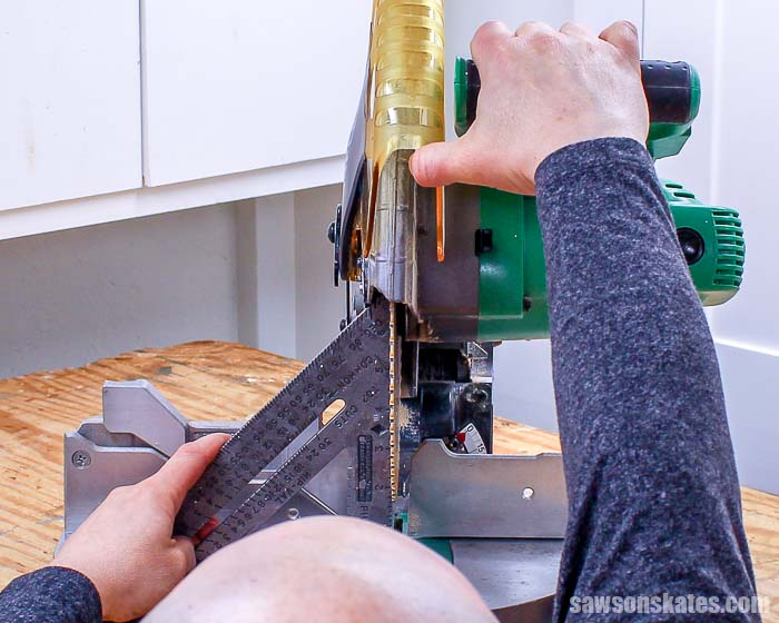 Using a speed square to sight down a miter saw blade to see if it is square to the table
