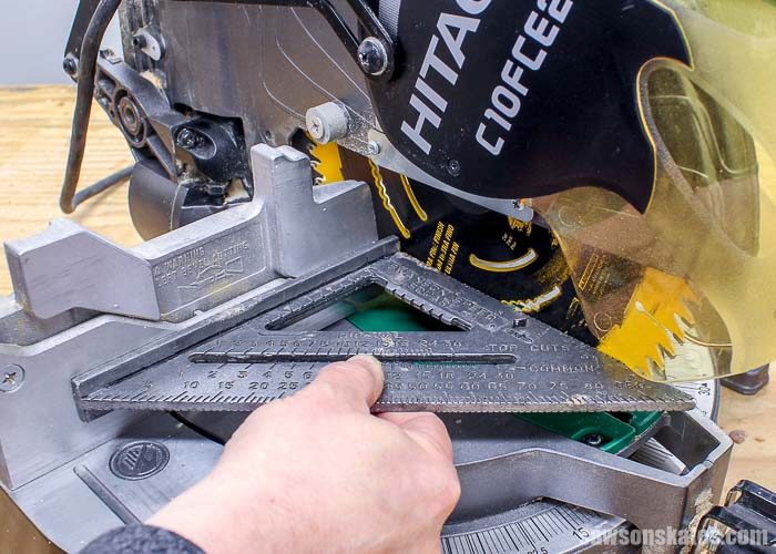 Using a speed square to check if the miter saw fence is square to the blade