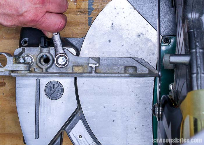 Loosening a bolt to square the miter saw fence to the blade