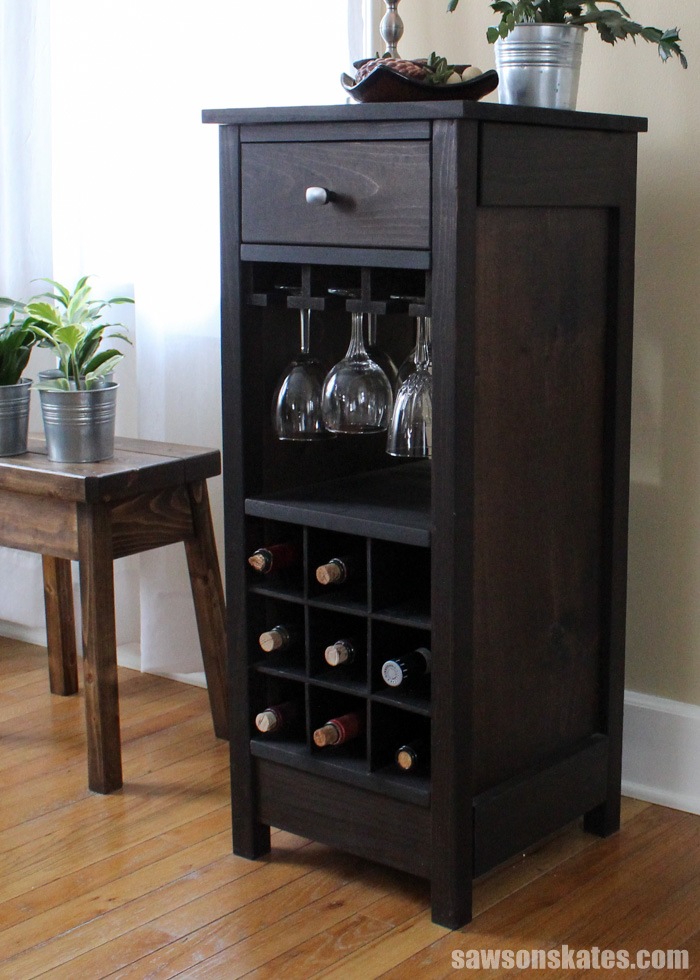 This wood DIY wine cabinet boasts nine spaces for wine bottle storage, three stemware holders for displaying up to 12 wine glasses and a drawer perfect for storing accessories like a bottle opener.