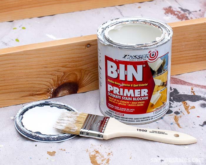 A container of BIN primer, paintbrush and a wood knot.