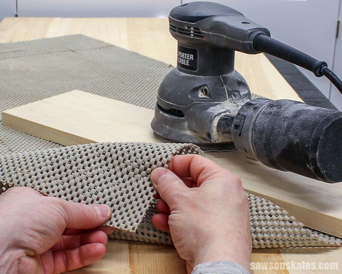 Sanding wood projects on a rubber router mat prevents parts from sliding