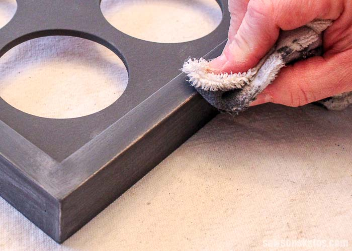 After spraying chalk-style paint a wet rag is used to distress the picture frame