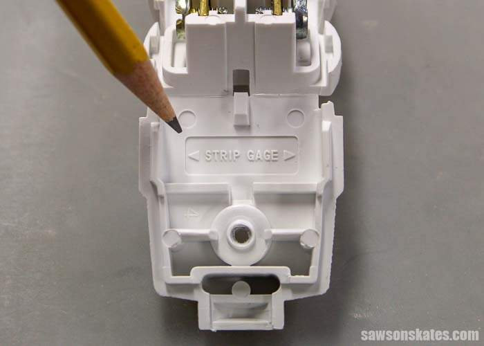 A replacement 2 prong plug has a strip gauge which shows how much of the insulation needs to be removed when wiring a plug