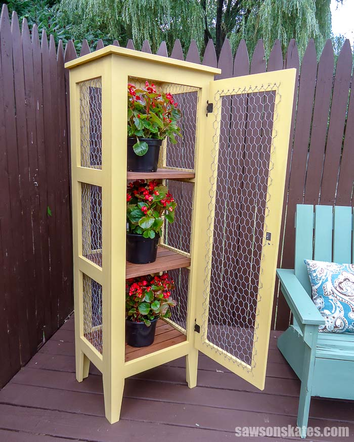 The door of this DIY outdoor plant stand is open showing the 3 tiers for displaying flowers
