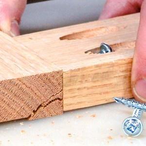 A pocket screw splitting a pocket hole in a piece of oak