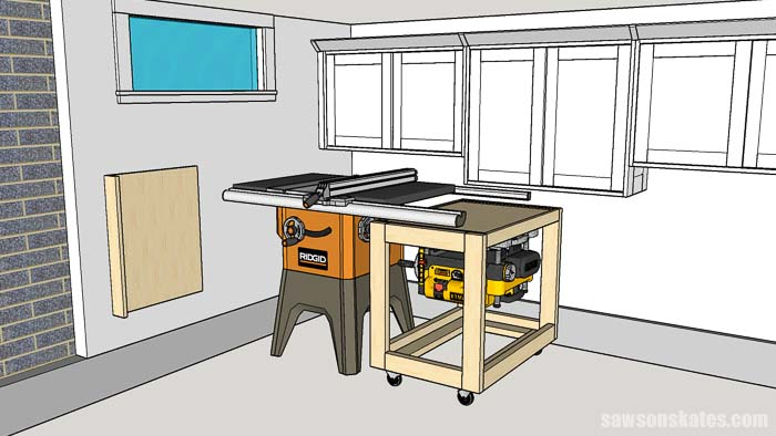 A flip top tool stand is stored under a table saw in this small woodshop layout