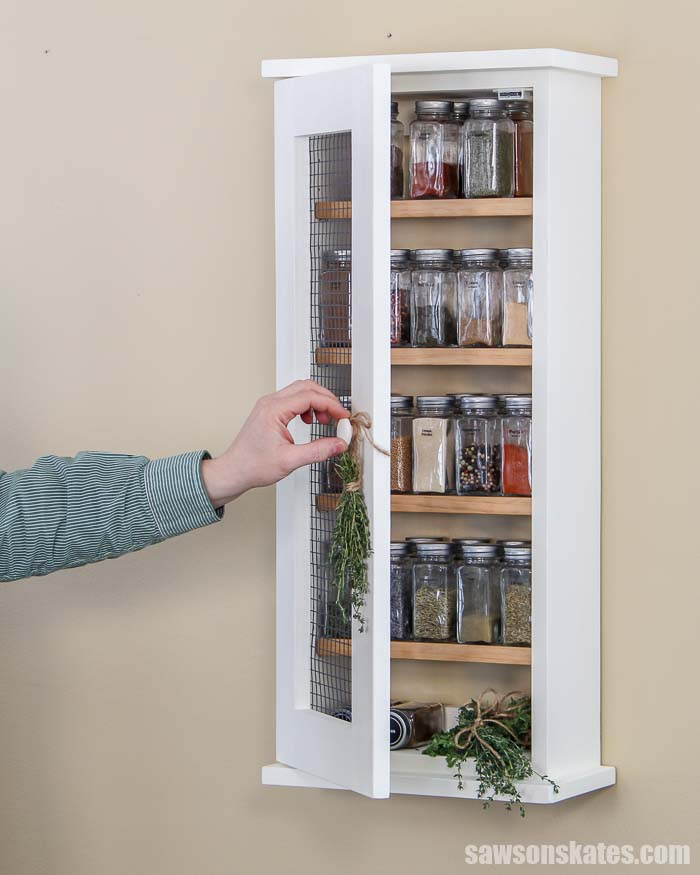 Build your own wall-mounted DIY spice rack with these free plans! This easy to build wood cabinet has a rustic chicken wire door and adjustable shelves.