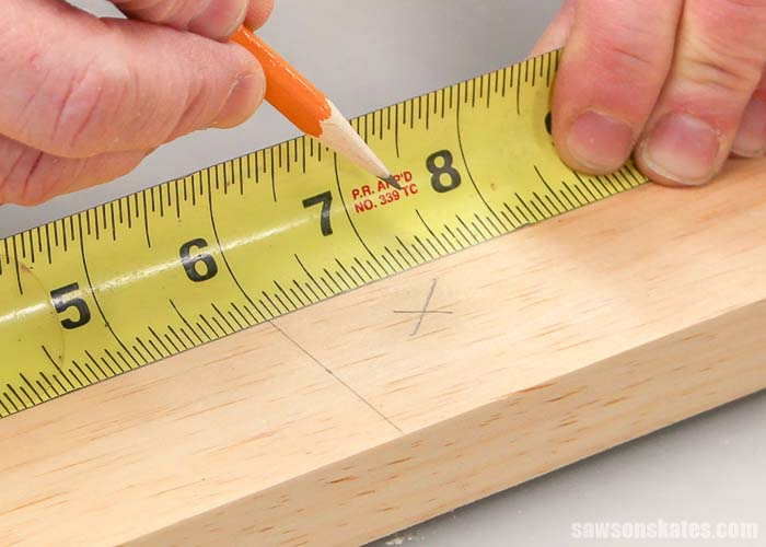 """The first step to cutting wood is to measure and mark an """"x"""" on the waste side"""