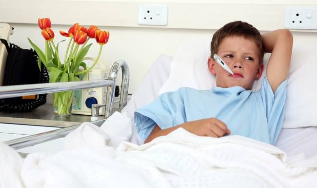 stock-footage-little-sick-boy-sitting-in-bed-with-thermometer-in-the-hospital-ward