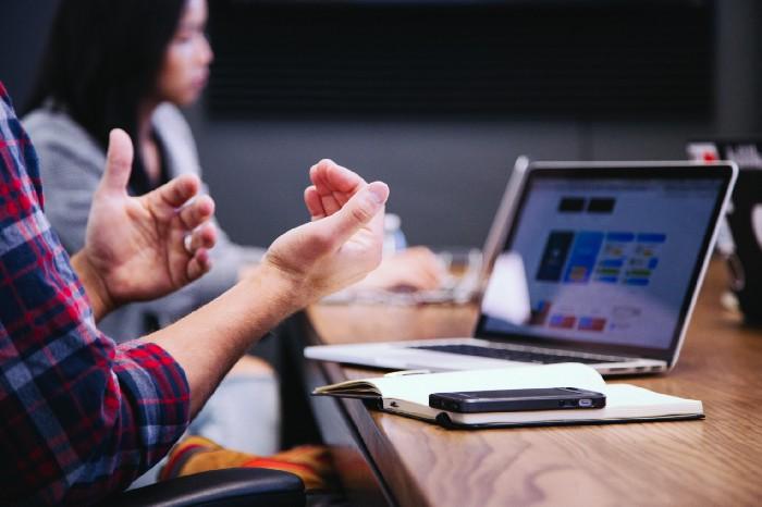 Un chico, solo se le ven las manos, explicando algo frente a una mesa con una computadora.