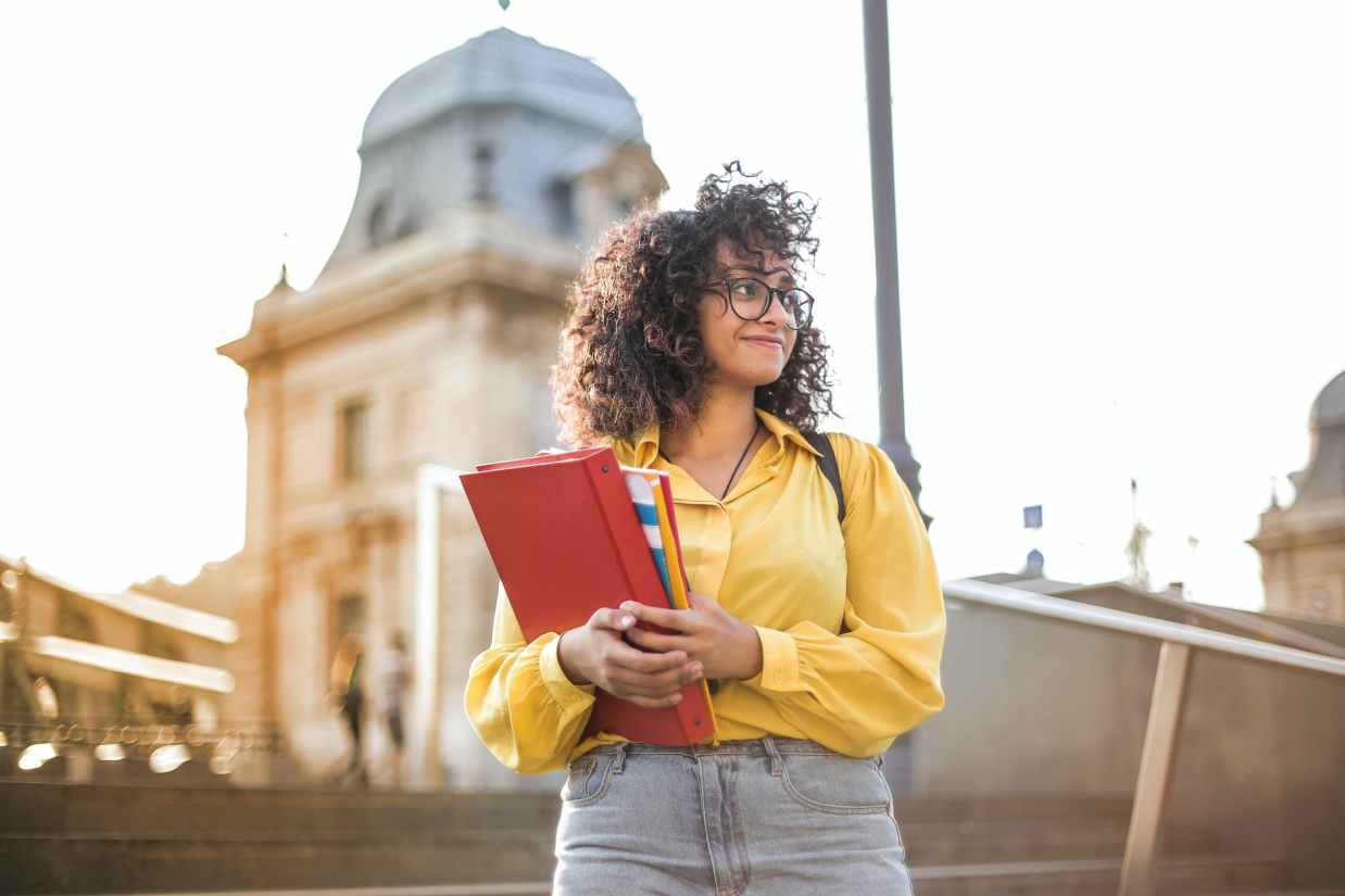 woman in yellow jacket holding red book