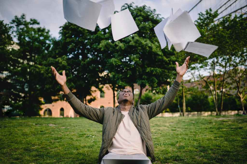 excited male student throwing university papers in air