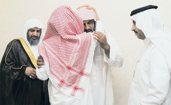 The murderer, Faisal al-Ameri, kissing the forehead of Rabi'a al-Dousary, the father of the young man he killed. (Credit: al-Yawm newspaper)