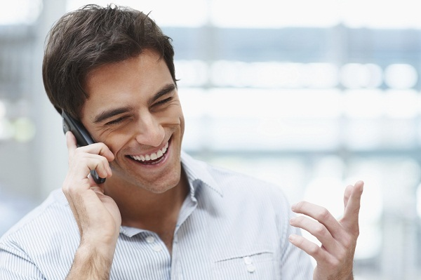 Laughing young guy enjoying a conversation over the cellphone