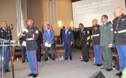 """USMC, Sgt William Farmer plays """"Taps"""" in memorial service."""