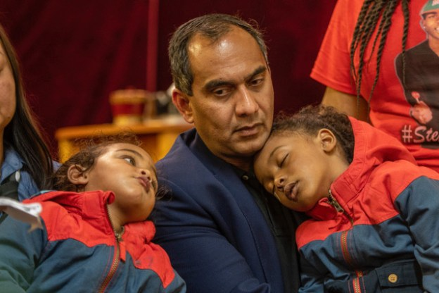 Grandfather Raj Manni holds the children of Stephon Clark during the press conference.