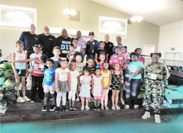 The law enforcement panelists are pictured with the children and the top row is Pastor Cooper and Vernall Townsend.