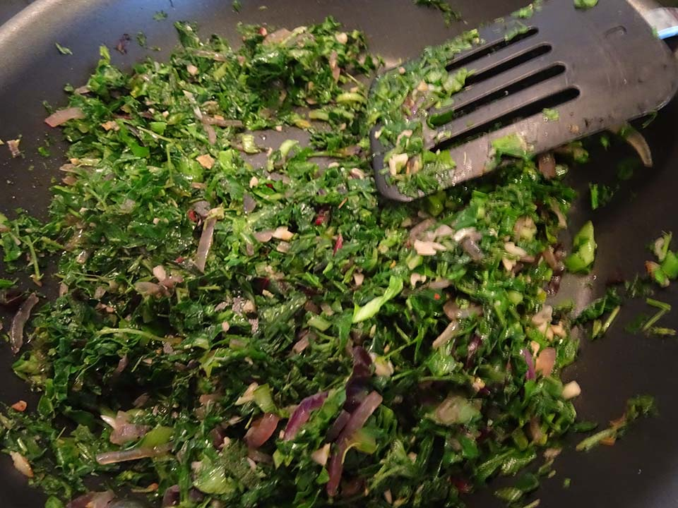 Wilting the weeds and greens with the onion and garlic