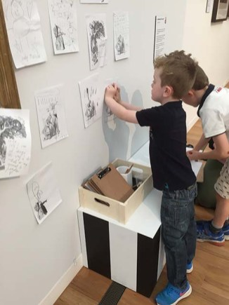 Cooper placing his work on the wall - r
